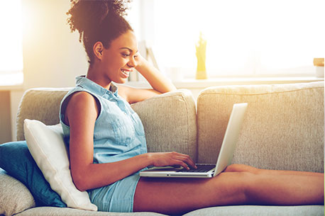 Surfing web at home. Side view of attractive young African woman working on laptop and smiling while sitting on the couch at home